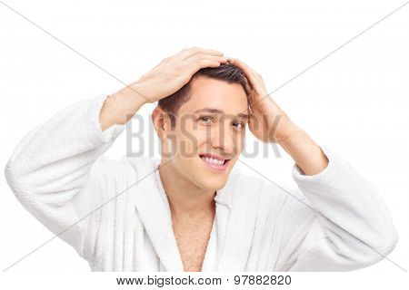 Young man in a white bathrobe making his hair and looking at the camera isolated on white background