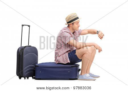 Young male tourist sitting on his luggage and looking at the time isolated on white background