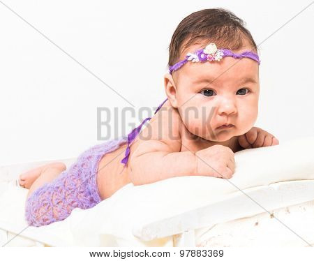 two-month-old girl in fishnet panties lying in bed