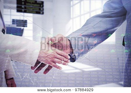 Close up of business people shaking their hands against stocks and shares