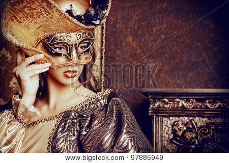 Venetian masquerade carnival. Elegant lady wearing beautiful lush dress and venetian mask stands in a palace room. Renaissance. Barocco. Fashion.