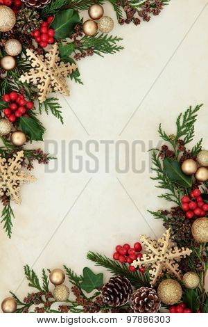 Christmas abstract background border with gold snowflake and bauble decorations, holly, fir and cedar cypress greenery over parchment paper.