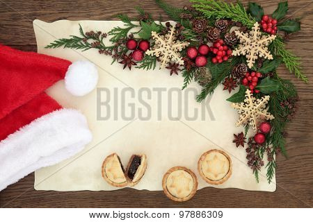 Christmas eve blank letter to santa with hat, mince pies, holly, bauble decorations and winter greenery on parchment paper over oak background.