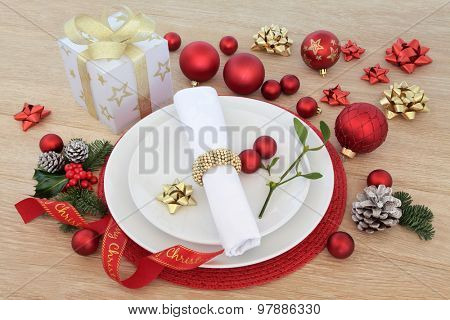 Christmas dinner place setting with plates, napkin, baubles and ribbon decorations with winter flora over oak background.