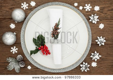Christmas dinner time with plate, napkin, sparkling silver bauble decorations, holly and winter greenery over oak table background.