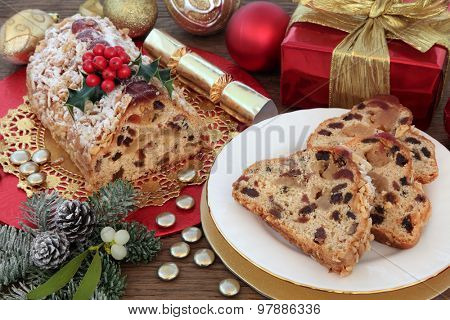 Stollen christmas cake with slices, red and gold decorations, holly, mistletoe and winter greenery.