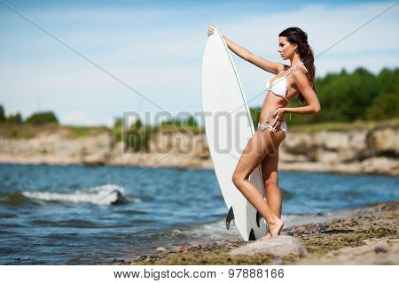 Sexy brunette girl in white swimsuit posing with a surfing board on a beach