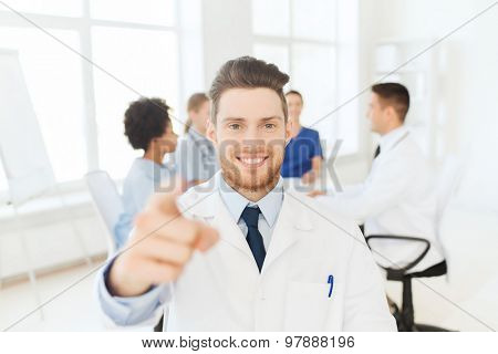 clinic, profession, gesture, people and medicine concept - happy male doctor pointing finger at you over group of medics meeting at hospital