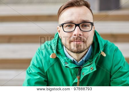 people, style, leisure and lifestyle - happy young hipster man in eyeglasses and jacket sitting on stairs in city