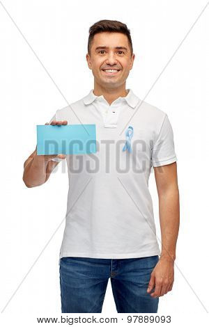 medicine, health care, gesture and people concept - middle aged latin man in t-shirt with sky blue prostate cancer awareness ribbon holding blank paper card