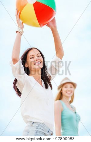 summer holidays, vacation and beach activities - girls playing ball on the beach