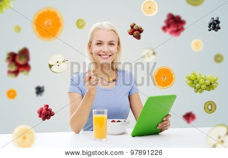 healthy eating, dieting and people concept - smiling young woman with tablet pc computer eating breakfast over fruits and berries on gray background