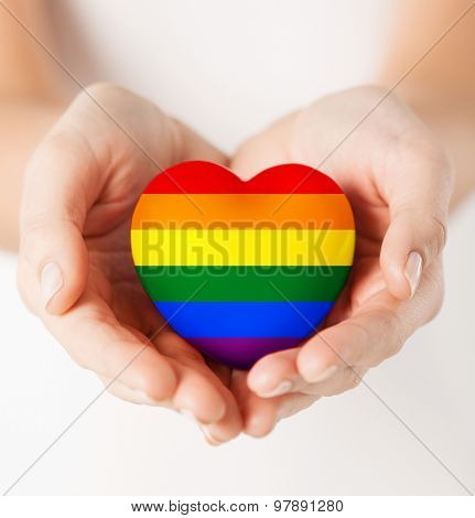 gay pride, homosexual, love and charity concept - close up of female hands holding small rainbow heart