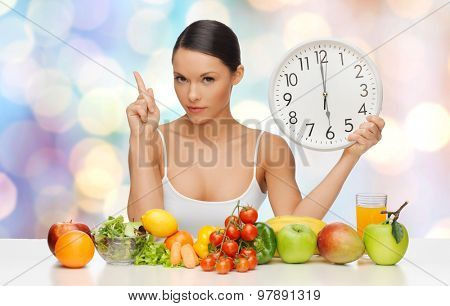 people, eating and diet concept - woman with healthy food holding big clock, pointing finger up and warning over blue lights background