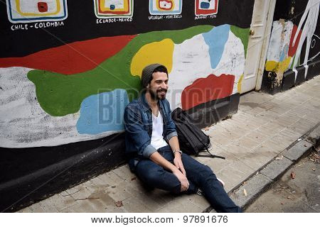 Young Stylish Student Seated Against A Colorful Wall.