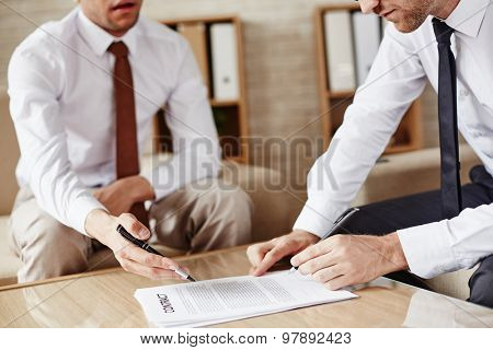 Businessman signing contract after discussing its terms with partner