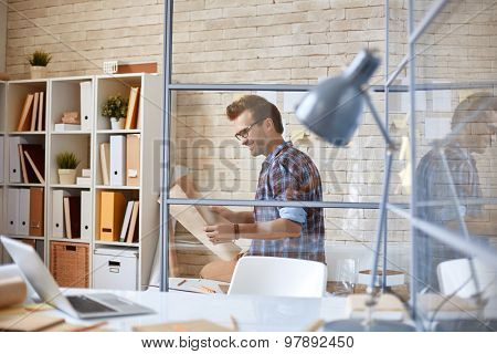 Handsome architect looking at unfolded blueprint in office