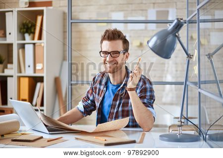 Young businessman with draft looking at camera at workplace