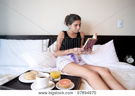 Woman Having Breakfast In Bed And Holding A Tablet