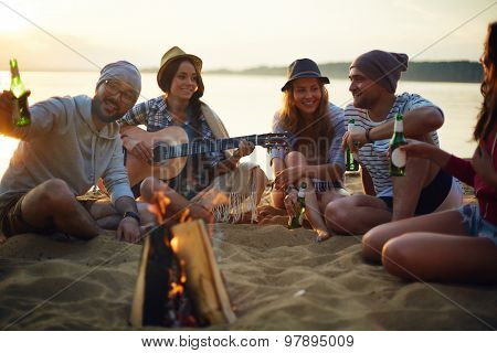 Happy friends with drinks and guitar sitting by campfire