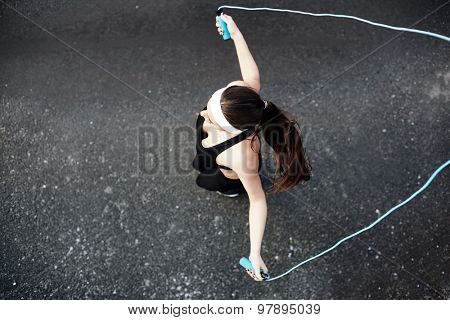 Girl in activewear exercising with skipping-rope