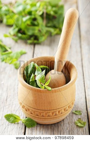 Fresh Mint In Wooden Mortar On Grey Wooden Background