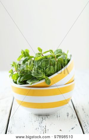 Fresh Mint In Bowl On White Wooden Background