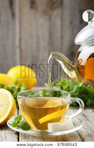 Pouring Tea Into Cup Of Tea On Grey Wooden Background