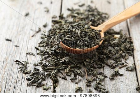 Dry Tea In Spoon On Grey Wooden Background