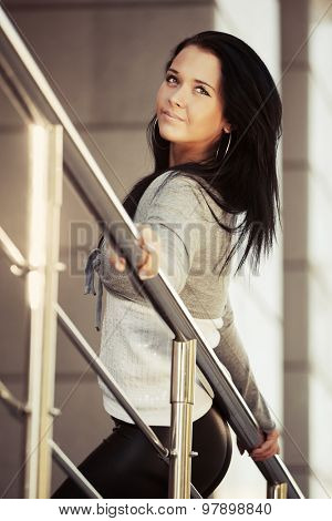 Happy young fashion woman leaning on handrail