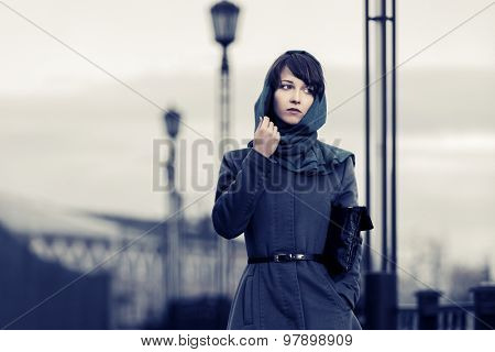 Sad young fashion woman in grey classic coat with handbag