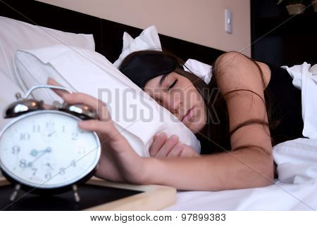 Young Woman Turning Off Alarm Clock