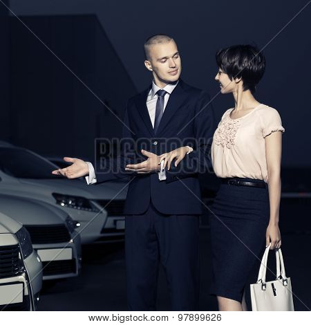 Young fashion business couple collecting new car at dealership lot