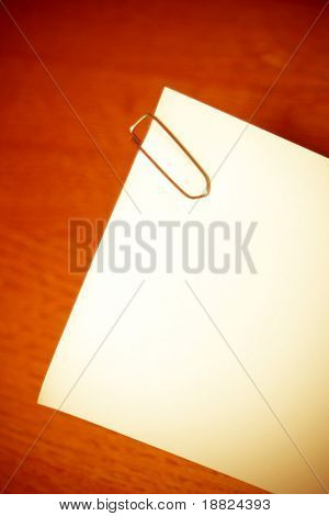 Blank note paper with staple on wooden background