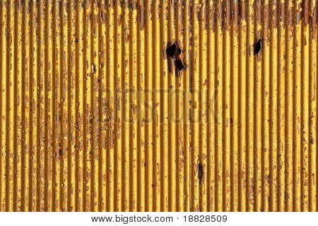 Rusty metallic background with shrapnel hole