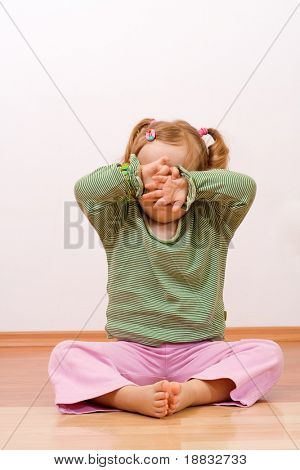 Little girl hiding behind her hands - sad or playful, with copyspace