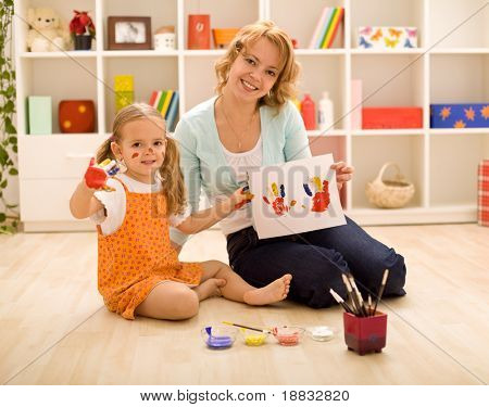 Woman and little girl painting hand and making prints- focus on the girl face