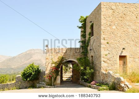 Entrance portico of an ancient abbey with the mountain in background on the island of Crete