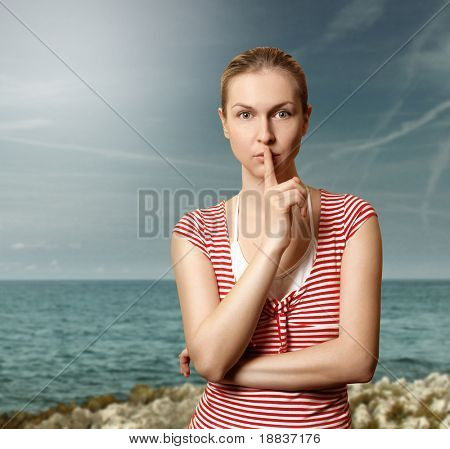 Sporty woman with finger near mouth on the beach