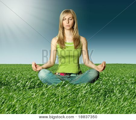 Blonde in lotus pose in green grass on blue summer sky