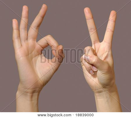 Female hands showing okay and victory gestures