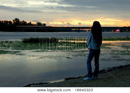 Woman alone standing on bank of river watching sunset