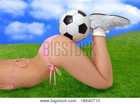 Sexy girl in bikini with soccer ball on her butt lying on green summer grass