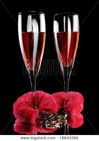 Two champagne flutes cuffed with red furry handcuffs romantic concept isolated on black background
