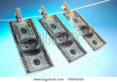 Hundred dollar bills drying on a clothes line isolated on blue sky background Money laundering concept