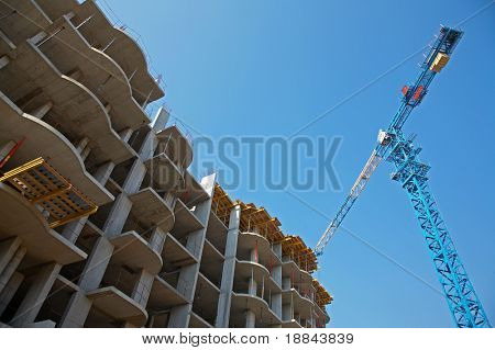 The elevating crane against the dark blue sky, building a monolithic building.