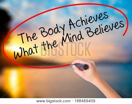 Women Hand Writing The Body Achieves What The Mind Believes With Black Marker On Visual Screen