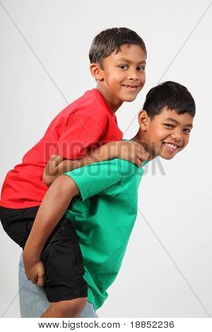 Playful young school mates giving piggy back