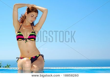 Portrait of a beautiful woman sunbathing by the swimming pool