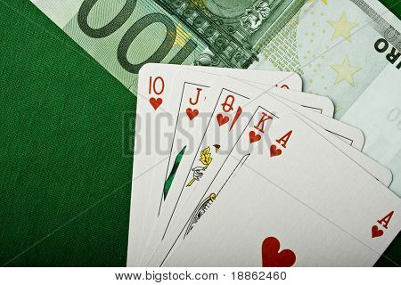 Royal flush hearts and money detail and green felt